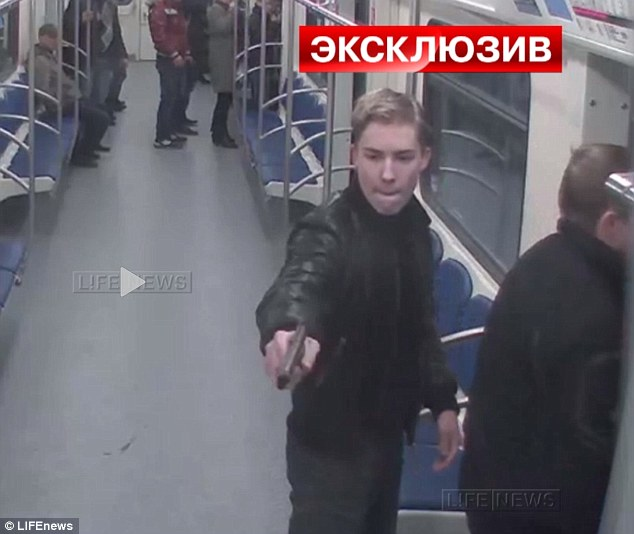 Fear: Fellow passengers on the Moscow Metro rush to the other end of the carriage as the second attacker also pulls out a weapon