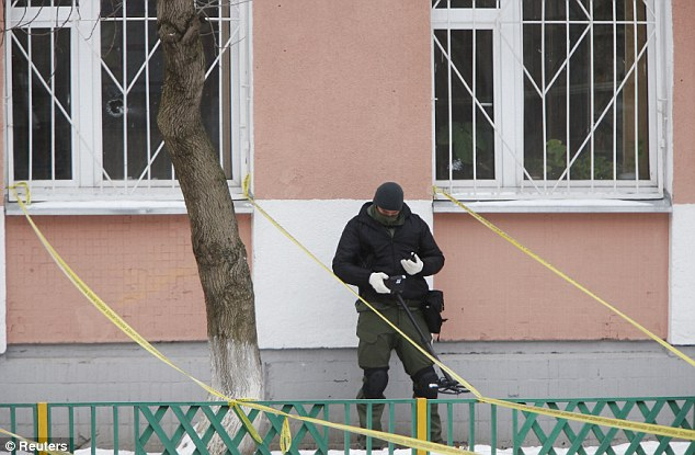 A security service member uses a metal detector near the building of a high school where a student shot his teacher and police officer
