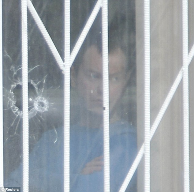 A man stands near a window with bullet holes at a high school in Russia where a student killed a police officer and a teacher